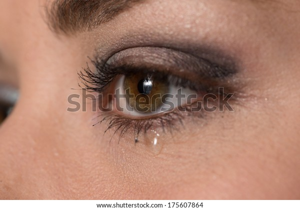 close up of the eye of a young woman with a tear drop on her lower eyelid