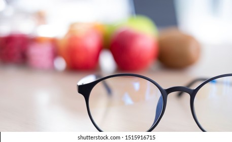 Close up eyeglasses with fruits & food supplement in background. The food supplements is for eyes care & remedy. To avoid eyes problems, patient need good nutrition. Healthcare & medical car concept.