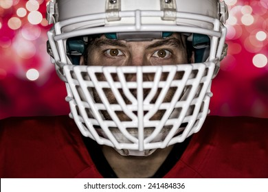 Close up in the eyes of a Football Player with a red uniform on a red lights background.