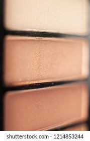 Close up of an eyeshadow pallet in a range of nude shades.  Shallow depth of field.  Vertical image.