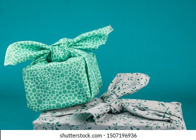 Close up of fabric wrapped gifts, resueable sustainable recycled textile gift wrapping alternative zero waste concept with copy space