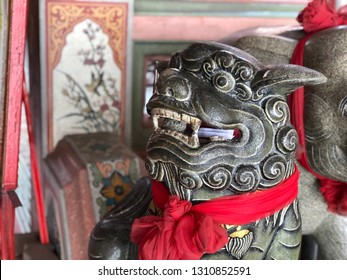 Close up face of ancient Dragon descendants statue, called Kylin or Qilin at the entrance to the Chinese shrine or temple. Exterior decorations, sculpture to protected the holy place. Selective focus.