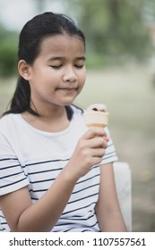 close up face of asian teenager with icecream cone in hand