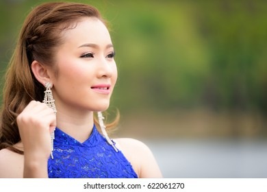 Close up to face Beautiful woman wear blue evening dress over mountains and rivers background.