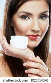 Close up face beauty portrait of young woman holding skin care cream jar.