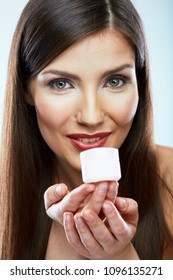 Close up face beauty portrait of young woman with long hair holding skin care white cream container.