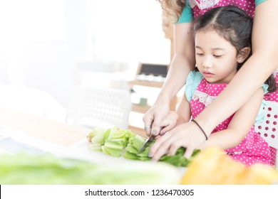 close up face of children , Asian children cooking organic salad with her mother, they use knife cut vegetable on chopping board, asian children  learning to cooking in kitchen room, family activity