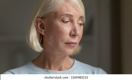 Close up face of elderly woman feels desperate abandoned and lonely having health or mental problem, lost in sad thoughts suffers misfortune, hard going through physical changes ageing process concept