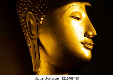 close up face of golden buddha statue in the light and shadow of sun at Wat Pra Sri Mahathat temple, Phitsanulok province, Thailand