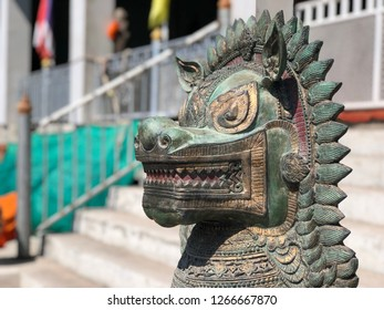 Close up face of Green Dragon descendants statue, called Kylin or Qilin at the entrance to the Chinese shrine or temple. Exterior decorations, sculpture to protected the holy place. Selective focus.
