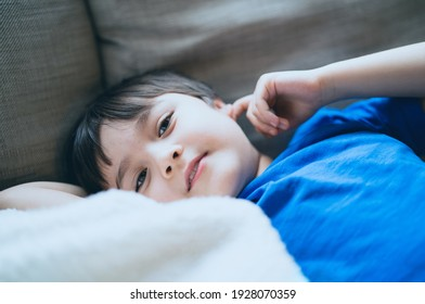 Close up face of kid looking at camera with smiling, A happy boy lying on sofa relaxing on weekend, Comfortable Child laying down on couch and looking out, Positive children concept