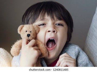 Close up face of Kid yawning and holding teddy bear, Sleepy child yawning and looking at cameta, Head shot tired child get a cold during weather change, Children health care concept