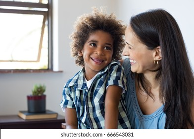 Close up face of latin woman playing with her african son. Happy young son feeling loved by mother. Portrait of a lovely mom and cute little black boy looking up at home. Adoption and family concept.