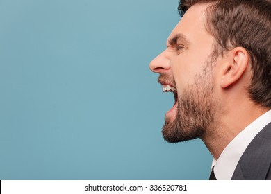 Close up of face of man shouting with anger. He is standing in profile. Isolated on blue background. Copy space in left side