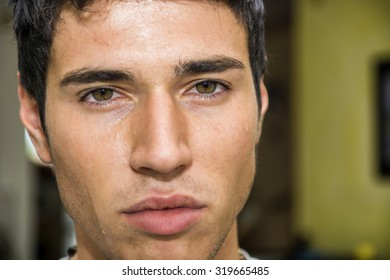 Close up Face of a Pensive Handsome Young Man with Tears on his Face, Looking at Camera, Worried or Sad.