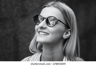 Close up face portrait of beautiful, cute attractive young model blondel in shirt, glasses and curly hair looking up. Isolated . Tenderness, femininity and charming.