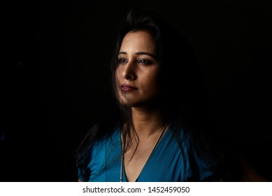 Close up face portrait of a beautiful Indian Bengali brunette woman in light and shadow before a black copy space background with her hair blowing in the wind. Indian lifestyle and fashion  portrait