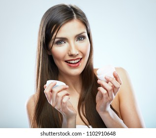 Close up face portrait in beauty style of smiling woman holding skin care cream. Isolated studio.
