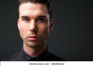 Close up face portrait of a handsome young man posing against gray background
