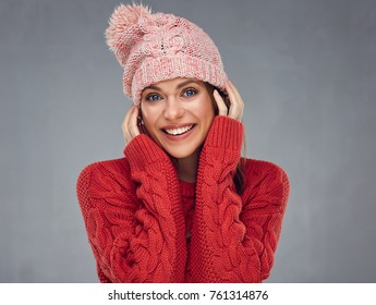 Close up face portrait of toothy smiling young woman wearing red sweater with pink knitted hat.