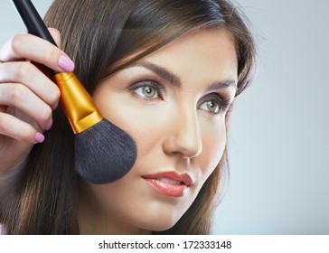 Close up face portrait of young beautiful woman. Make up brush. Isolated background.