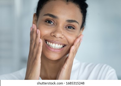 Close up face pretty African woman touches her perfect flawless skin. Result after mask cream beauty spa treatment, aesthetic medicine, chemical peeling, anti wrinkle procedure or product ad concept