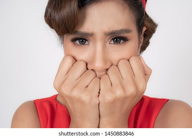 Close up face of pretty Asian woman lift up two hands and gagged by fear, The eyes looking to camera on white background