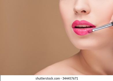 Close up of face of pretty young woman with naked shoulder. The make-up artist is applying bright pink lipstick on her lips with a brush. Her mouth is slightly open. Isolated