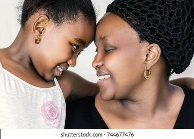 Close up face shot of african mother and daughter looking at each other. Tender close up portrait of kid going head with mother isolated against white background.