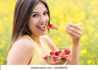 Close up face shot of attractive young woman eating healthy crispy whole grain cereal breakfast outdoors.