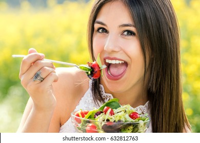 Close up face shot of attractive young woman eating green salad outdoors. Girl with open mouth about to take a bite.