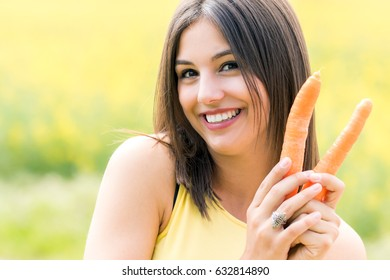 Close up face shot of attractive young woman holding organic carrots outdoors.