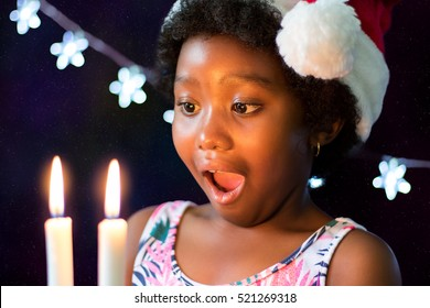 Close up face shot of exited little african girl looking at candles glowing in the dark. Low lift portrait of child wearing christmas hat against star background.