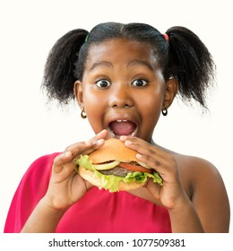 Close up face shot of expressive little african girl with open mouth and big eyes about to eat hamburger.Kid holding meat hamburger infant of face isolated on white background.