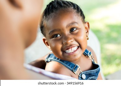 Close up Face shot of little african girl laughing. Child looking at out of focus mother.