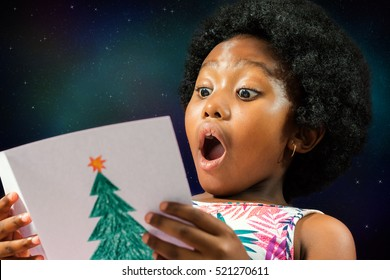 Close up face shot of little african girl reading a christmas card with surprised face expression.Excited kid with mouth open against galaxy star background.