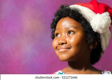 Close up face shot of little african girl wearing christmas hat. Kid staring at upper corner against star burst background.