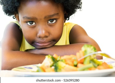 Close up face shot of little afro american girl with negative moody face expression at dinner table. Kid pulling funny face with vegetable dish in foreground. Isolated on white.
