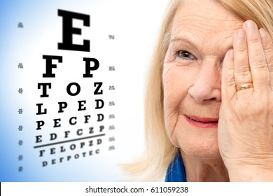 Close up face shot of senior woman reviewing eye sight with vision test chart in background.