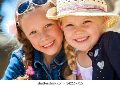 Close up face shot of two young girlfriends smiling with heads together outdoors.
