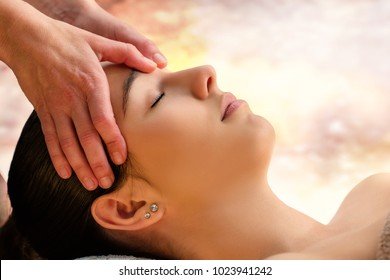 Close up face shot of woman enjoying facial therapy in spa.Therapist massaging fore head with thumbs.