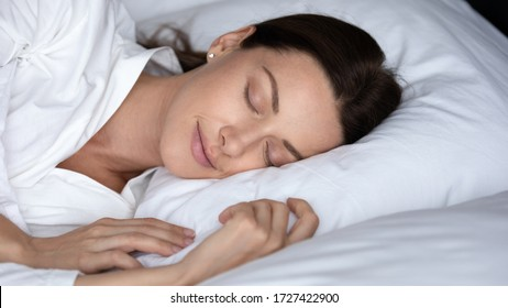 Close up face sleeping gorgeous carefree well-groomed woman with healthy skin fall asleep in bed see dreams, 30s female smile enjoy enough of rest, fresh sheets, soft bedding, natural beauty concept