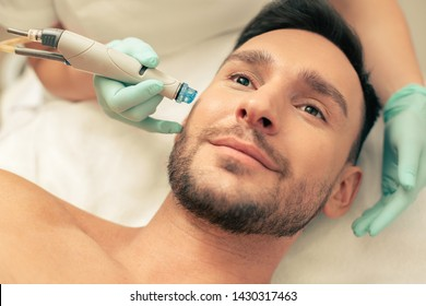 Close up of the face of a smiling bearded man undergoing a pleasant skin nourishing procedure