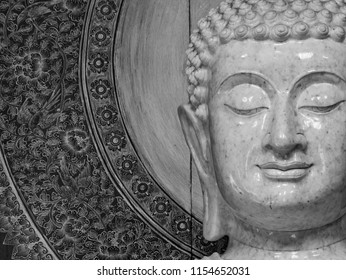close up face of white marble buddha statue in black and white color