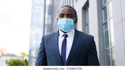 Close up of face of young African American handsome businessman in medical mask looking straight to camera with happy look. Portrait of man at street. Coronavirus concept.