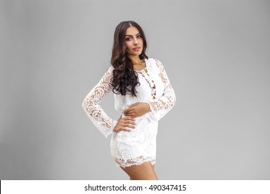 Close up face. Young arabic woman in white sexy dress, isolated on gray background