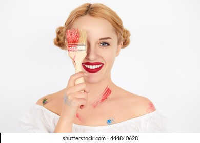 Close up face of young blond woman painter holding a paint brush over her eye on white background. Bright clean makeup.