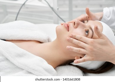 Close up of face of young, pretty woman and hands of beautician making massage. Patient  lying on massage table, looking up. Concept of skin care and rejuvenation.