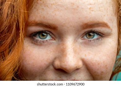 Close up face of young red ginger freckled woman with ginger hair and perfect healthy freckled skin, looking at camera with pretty cute smile