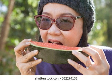 close up face of young woman eating water melon